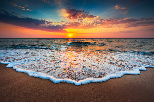 beautiful sunrise over the sea - wave stock photos and pictures