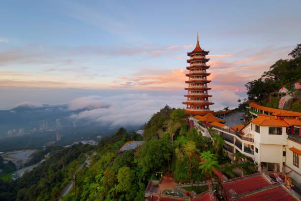 de weergave van de prachtige zonsopgang bij de chinese kin swee grotten tempel in genting highlands. het is een beroemde openbare toerisme plek in maleisië. - maleisië stockfoto's en -beelden