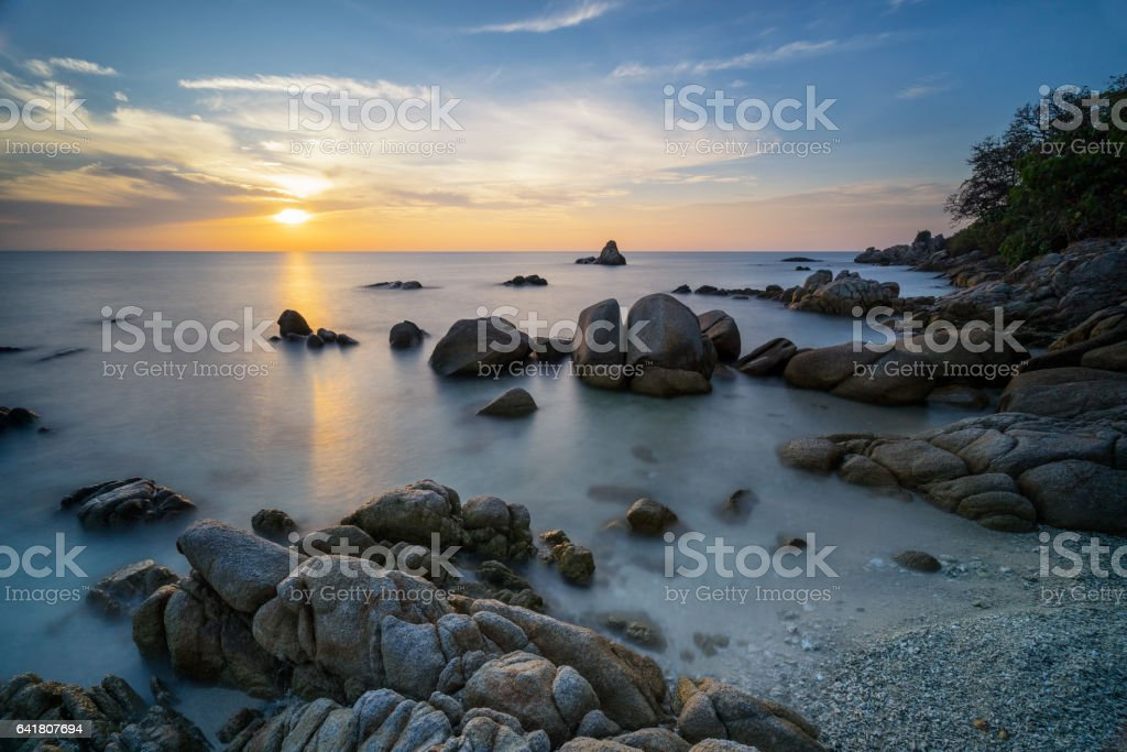 Beautiful sunrise with black rock at Eastern sea of Thailand stock photo
