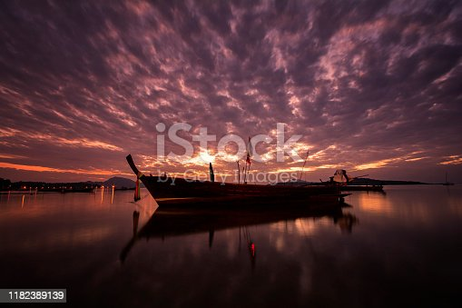 Beautiful sunrise with long tail boat on morning time, beach and sea with mountain background