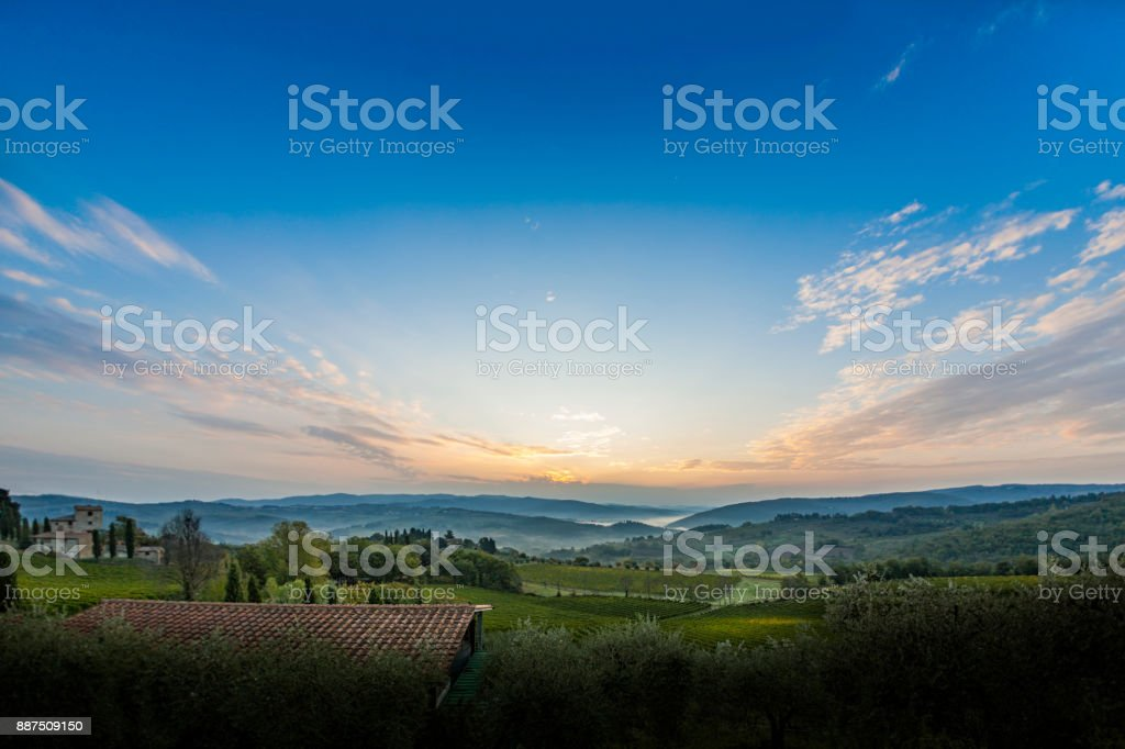 Beautiful sunrise with some fog between the hills with vineyards in Tuscany in Italy stock photo
