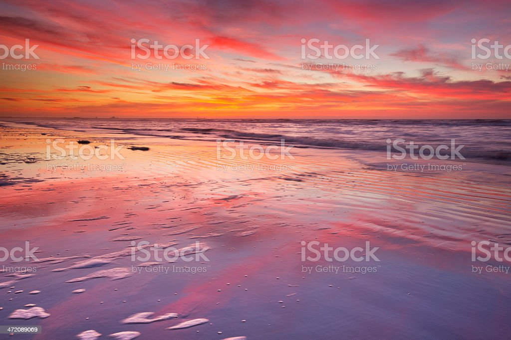Beautiful sunset and reflections on the beach at low tide royalty-free stock photo
