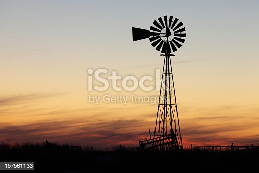 Windmill silhouette against warm sunset and cloudscape.