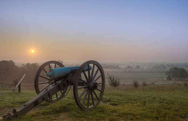 Beautiful sunset at Gettysburg Dawn over the Gettysburg battlefield, cannon standing guard. american civil war stock pictures, royalty-free photos & images