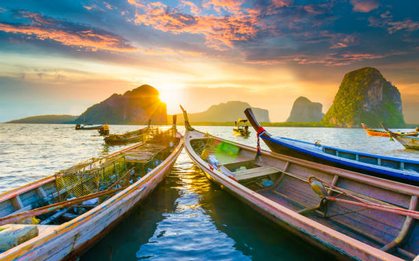 beautiful sunset at tropical sea with long tail boat in south thailand - phuket stock photos and pictures