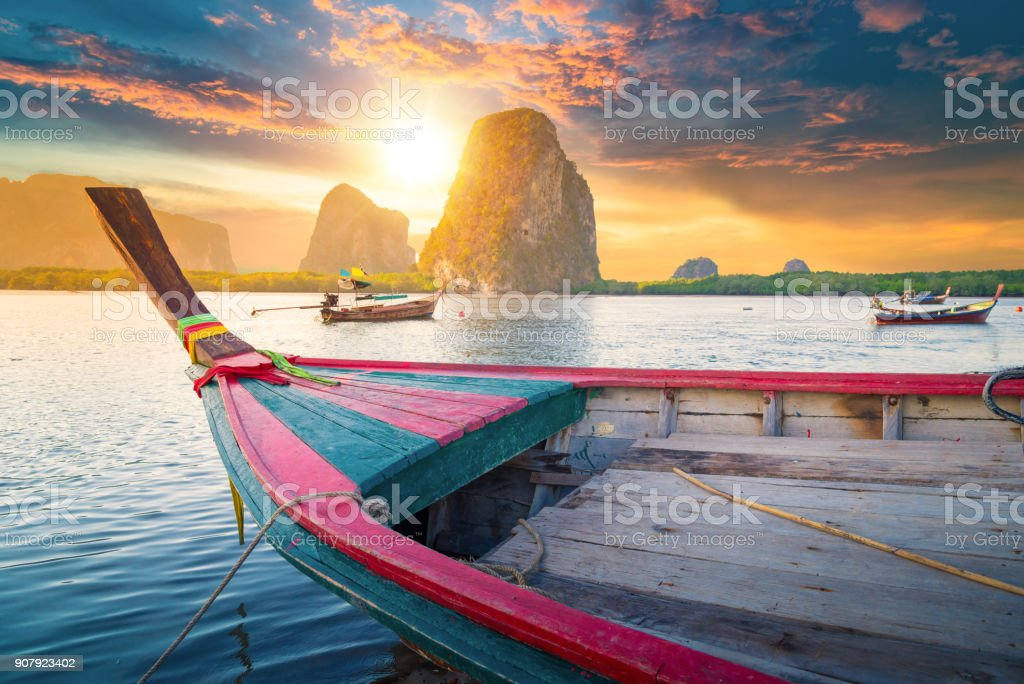 Beautiful sunset at tropical sea with long tail boat in south thailand stock photo