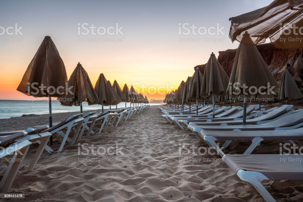 Beautiful sunset in Algarve Portugal.  Beach and cliffs with closed sun umbrellas. royalty-free stock photo