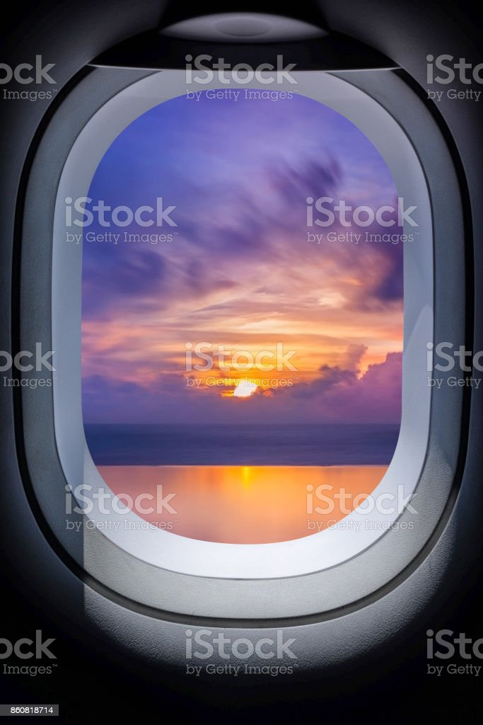 Beautiful sunset in seascape from aircraft window stock photo