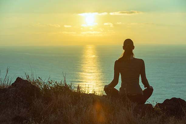 Beautiful sunset meditation Young woman meditating by the ocean at beautiful sunset.  prayer pose yoga stock pictures, royalty-free photos & images