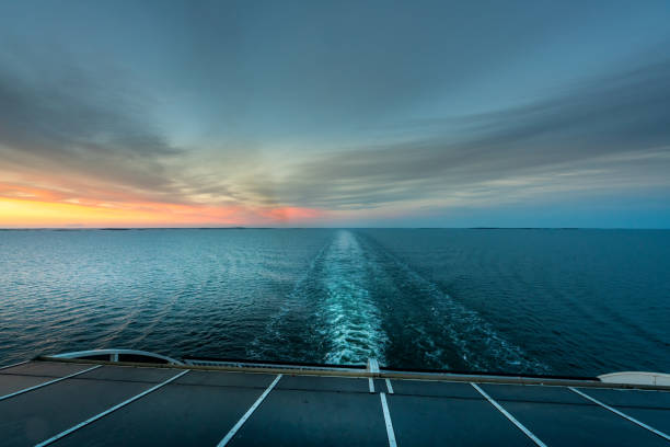 Beautiful sunset ocean view of the horizon with ship's wake seen from the back of a cruise ship. stock photo