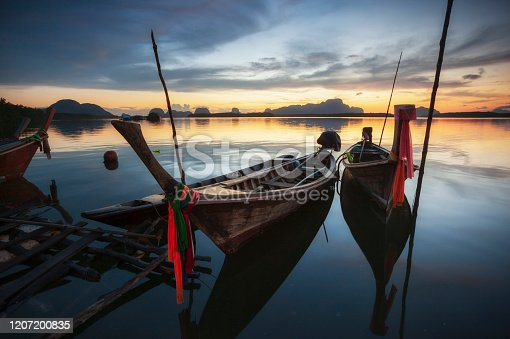 Beautiful sunset of fishing village in Phang Nga Bay with longtail wooden fishing  boat ,Thailand