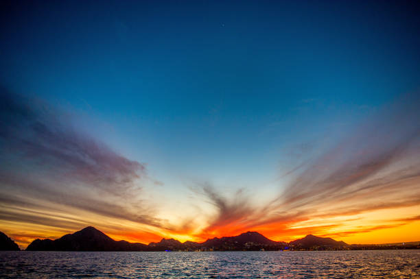Beautiful Sunset of Seascape with Mountains silhouets. stock photo