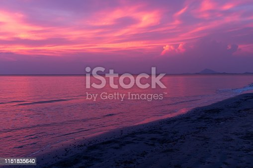 A beautiful sunset on a beach in Koh Lanta, Thailand, the sky ablaze with purples and blues reflected in the ocean, nobody in the image
