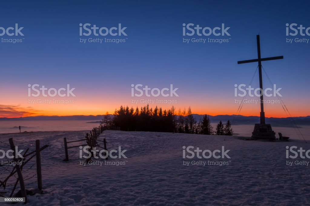 Beautiful sunset on summit cross of snow covered mountain Schoeckl stock photo