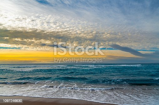 Idyllic scene, colorful sunset over the sea, beautiful sand beach, and colorful cloudy sky