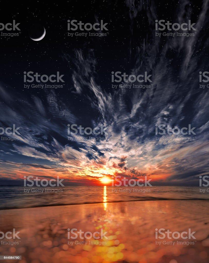 Beautiful sunset on the beach, stars and moon on the sky stock photo