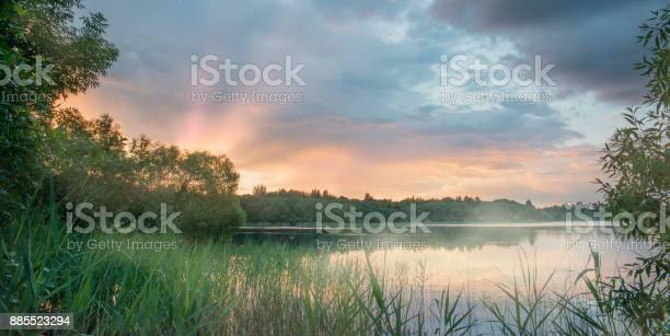 Photo of Beautiful sunset on the lake. The mist over the river.