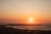 Wide shot of a beautiful sunset over an ocean, hills, islands, tropical city and its beaches.