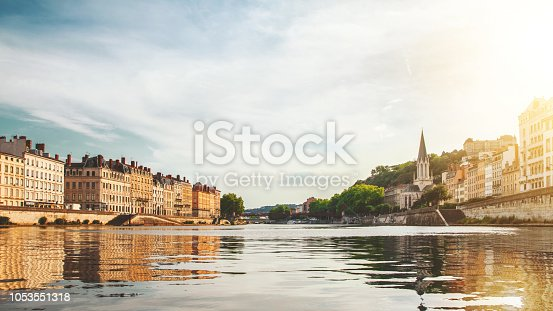 Color photography of Lyon city buildings, french culture architecture and wonderful ancient monuments in France, in Rhone, Auvergne-Rhone-Alpes region, seen from a boat on Saone river point of view in summer. Image taken from public area outdoors, along riverbank.