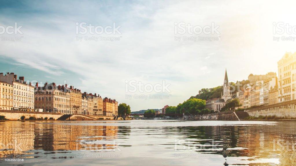 Beau coucher de soleil sur les bâtiments de ville de Lyon avec l'église St Georges à droite en France, vu du point de vue de Saone river - Photo