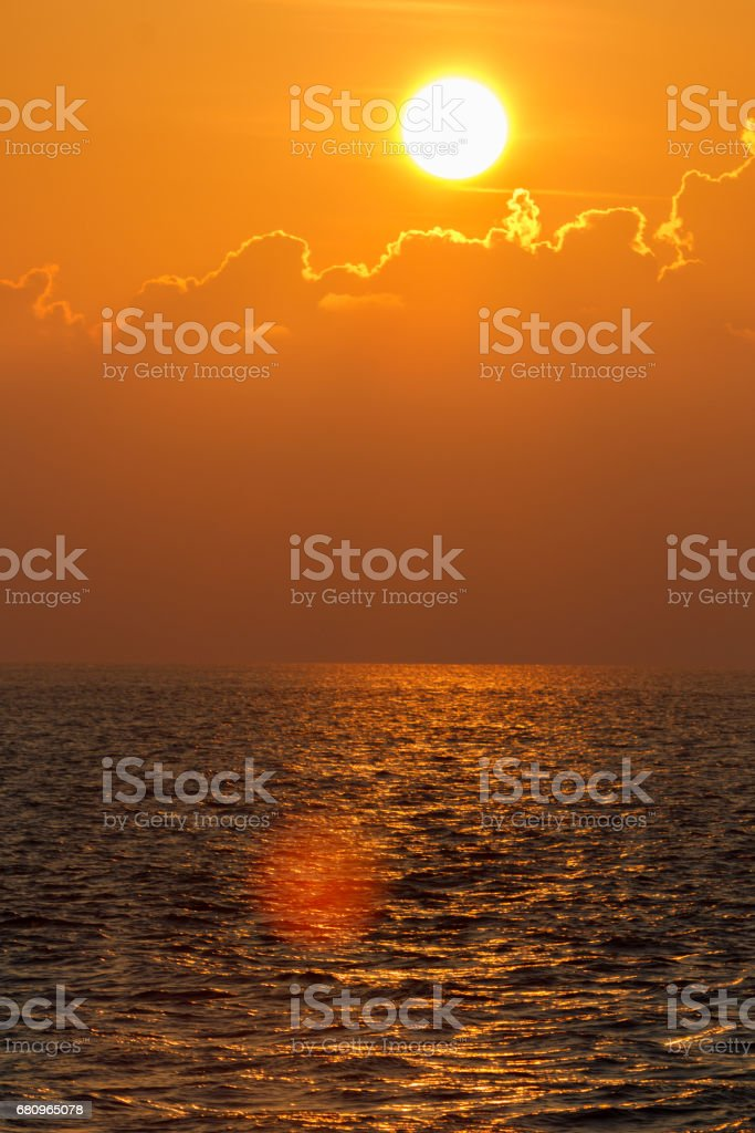Beautiful sunset over sea with reflection in water, colorful clouds in the sky royalty-free stock photo