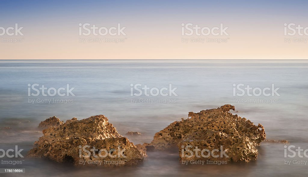 Beautiful sunset over Summer ocean with rocks and vibrant colors royalty-free stock photo
