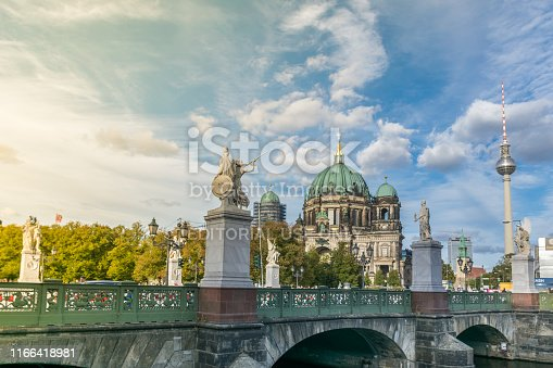 BERLIN, GERMANY - July 28, 2018: Beautiful sunset over the access to the Museum Island complex through the Schloss bridge and its statues, with the Berliner Dom and the TV Tower in the background.