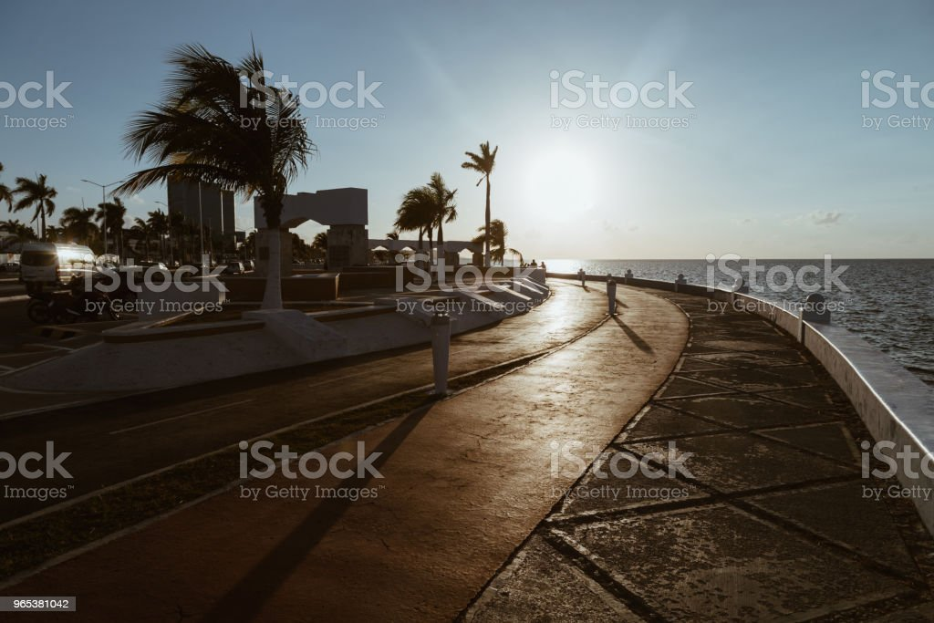 美麗的日落在海和城市。在海濱的跑步機和自行車路 - 免版稅人造堤岸圖庫照片