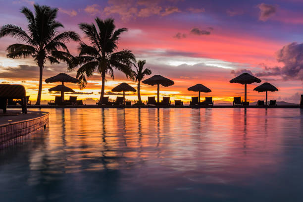 a beautiful sunset reflecting in the water in fiji - fiji stock photos and pictures