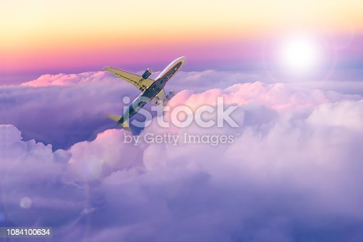 1045890176 istock photo Beautiful sunset sky above clouds with a plane moving upwards. Tourism and travel image. 1084100634