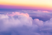 Beautiful sunset sky above clouds with nice dramatic light. View from airplane window.