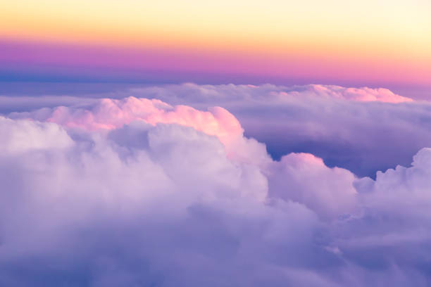 Beautiful sunset sky above clouds with nice dramatic light. View from airplane window stock photo