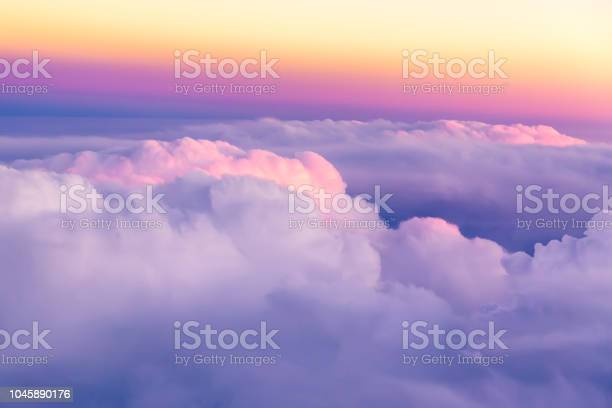 Photo of Beautiful sunset sky above clouds with nice dramatic light. View from airplane window