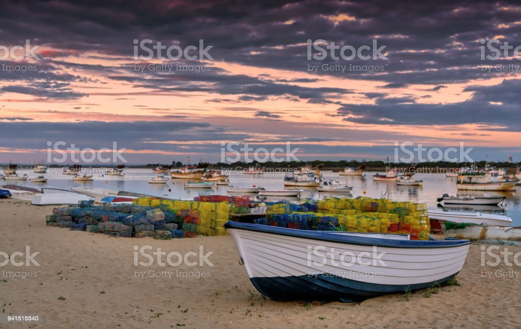 Beautiful sunset sky over fishing boats on the beach in Punta Umbria, Spain. stock photo