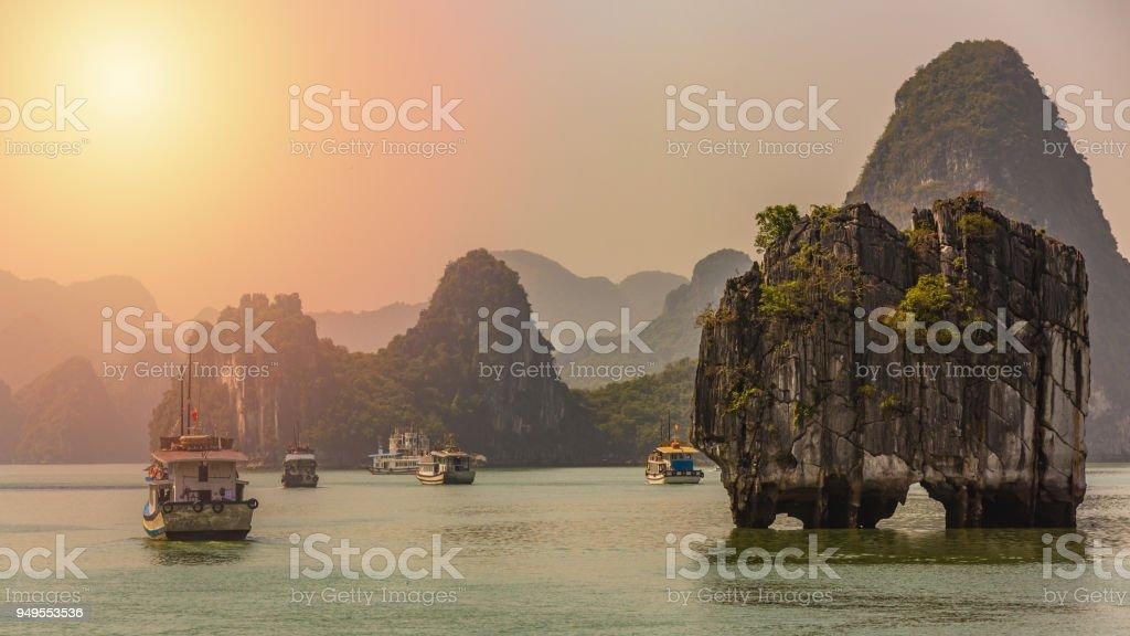 Hermoso atardecer juncos turístico, flotando entre las rocas de piedra caliza en el sudeste de la bahía de Ha Long, mar de China meridional, Vietnam, Asia. - foto de stock