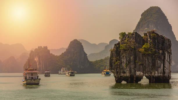 beautiful sunset tourist junks floating among limestone rocks at ha long bay, south china sea, vietnam, southeast asia. - oceano pacifico foto e immagini stock