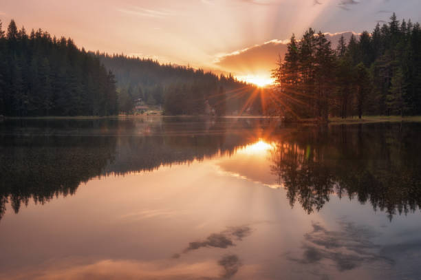 Beautiful sunset view with sun rays over a mountain lake. Shiroka Polyana dam in Rhodopi Mountains, Bulgaria. stock photo
