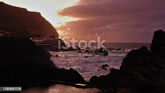 Beautiful sunset with dramatic sky above Porto Moniz on northwestern coast of Madeira island, Portugal with the popular natural swimming pools between rocks flooded by the wild surf of Atlantic Ocean.
