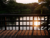 istock Beautiful sunset with the reflection on the water surface seen from wooden deck with fence 1177327058