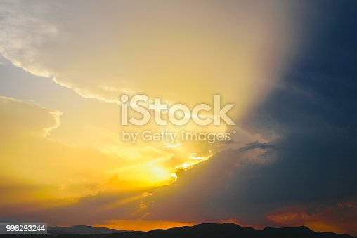 1013154212istockphoto Beautiful sunset with the sun of orange tones behind the mountains and deep blue sky 998293244