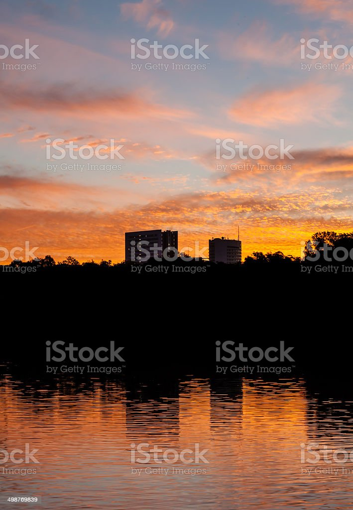 Beautiful Sunset with Two Buildings and Trees Reflected in Lake royalty-free stock photo