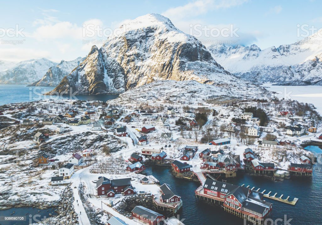 Beautiful super wide-angle winter snowy view of fishing village A, Norway, Lofoten Islands, with skyline, mountains, famous fishing village with red fishing cabins, Moskenesoya, Nordland stock photo