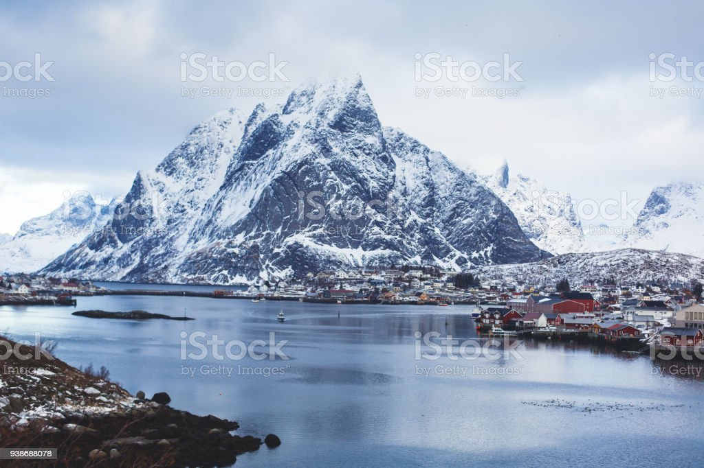 Beautiful super wide-angle winter snowy view of Reine, Norway, Lofoten Islands, with skyline, mountains, famous fishing village with red fishing cabins, Moskenesoya, Nordland stock photo