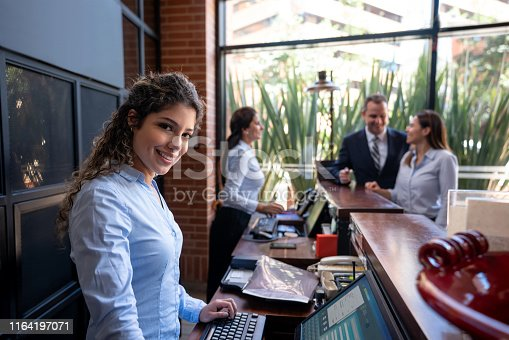 istock Beautiful supervisor at a hotel facing camera smiling and customer couple at background checking in with a receptionist 1164197071