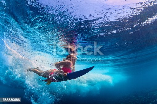 istock Beautiful surfer girl diving under water with surf board 583830686