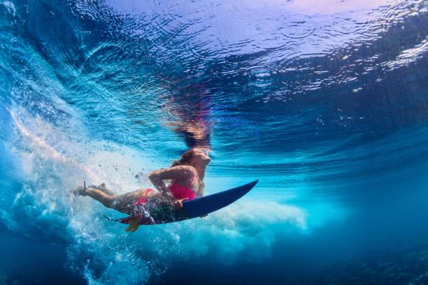 linda surfista menina mergulhando debaixo d'água com prancha de surf - esporte aquático - fotografias e filmes do acervo