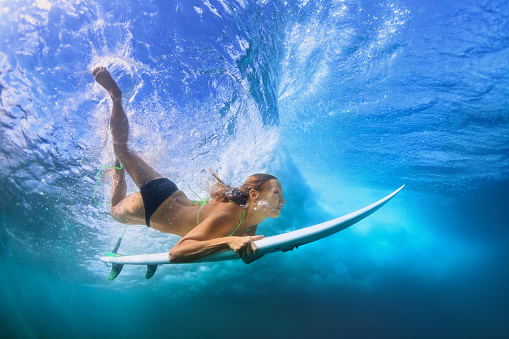 istock Beautiful surfer girl diving under water with surf board 586162010