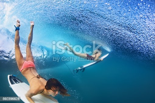 istock Beautiful surfer girl diving under water with surf board 592396628