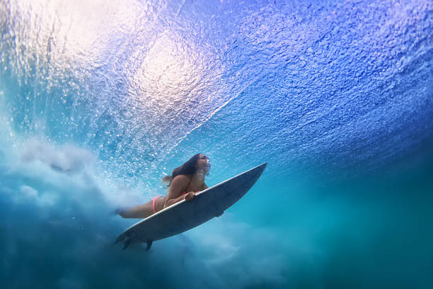 Beautiful surfer girl diving under water with surf board - Photo