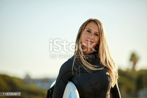 Portrait of confident mid adult woman wearing wetsuit while carrying surfboard. Beautiful female surfer is smiling at beach. She is having blond hair against clear sky.